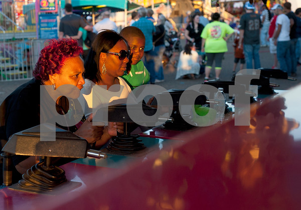 Tyler resident Cheryl Franklin, Trevescia King and Ryan Jones, 10, play a game at the East Texas State Fair in Tyler, Texas Thursday evening Oct. 1, 2015. The fair closes Sunday night.  (Sarah A. Miller/Tyler Morning Telegraph)