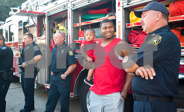 O'Neal Jones III and son O'Neal Jones IV talk with fire captain W.D. Davis of Tyler Station 2 during the Woodlands Apartments Texans Against Crime block party in Tyler, Texas Tuesday Oct. 13, 2015. Over 100 block parties were scheduled to take place Tuesday in Tyler. The block parties encourage neighbors to get to know each other which can help reduce crime in the community.   (Sarah A. Miller/Tyler Morning Telegraph)