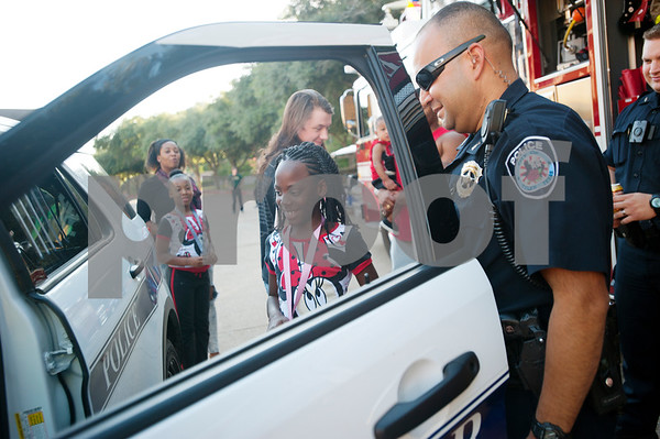 Imani Blackwell, 9, gets a tour of a police car from Tyler police officer Luis Aparicio during the Woodlands Apartments Texans Against Crime block party in Tyler, Texas Tuesday Oct. 13, 2015. Over 100 block parties were scheduled to take place Tuesday in Tyler. The block parties encourage neighbors to get to know each other which can help reduce crime in the community.   (Sarah A. Miller/Tyler Morning Telegraph)