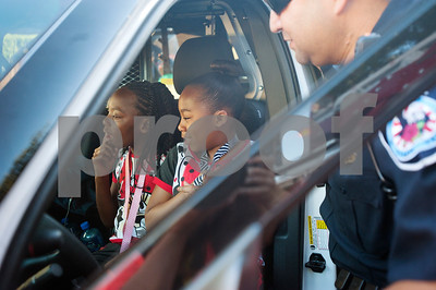 Sisters Imani Blackwell, 9, and Aniya Blackwell, 10, get a tour of a police car from Tyler police officer Luis Aparicio during the Woodlands Apartments Texans Against Crime block party in Tyler, Texas Tuesday Oct. 13, 2015. Over 100 block parties were scheduled to take place Tuesday in Tyler. The block parties encourage neighbors to get to know each other which can help reduce crime in the community.   (Sarah A. Miller/Tyler Morning Telegraph)