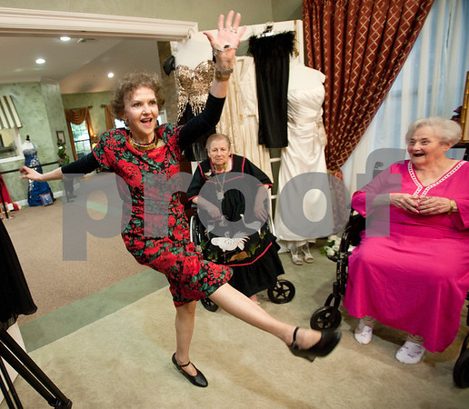 photo by Sarah A. Miller/Tyler Morning Telegraph  Prestige Estates community relations liaison Jo Anne McMeans gives residents a demonstration of the Charleston kick dance during the Rose Tea event at Prestige Estates Assisted Living in Tyler Tuesday afternoon. The event included hot tea and snacks, a bow demonstration by 1989 Texas Rose Festival lady-in-waiting Irene Epperson Leach and a show of evening and special occasion gowns from Ms. Texas Senior America competitors as well as gowns from previous Texas Rose Festival events. Several of the gowns on display hold special meaning for Prestige Estates residents such as the Pink Prestige Passion gown, which greeted guests at the front door and served as a symbol of breast cancer awareness and a reminder for women to schedule mammograms. The Texas Rose Festival kicks off Thursday at the Tyler Rose Garden Center.