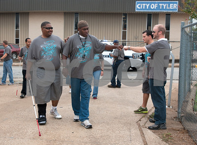 photo by Sarah A. Miller/Tyler Morning Telegraph  Sighted Horizon Industries employee Rodger Johnson of Tyler gives a fist bump employee Chris Ledding as he walks with visually impaired co-worker Curlie Bailey in the annual White Cane Walk Monday October 15 in downtown Tyler, Texas. The event was held by The Lighthouse, an East Texas nonprofit that assists blind residents in the community. The annual walk honors White Cane Day, nationally designated as Oct. 15, by President Lyndon B. Johnson recognizing the importance of the white cane as a symbol of independence for blind people. Horizon Industries is a division of The Lighthouse that employs blind and visually impaired people.
