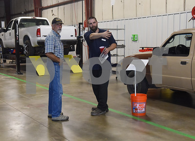 Production manager Brandon Kirksey, right, gives Rob Pinkham a tour of Vehicle Reman during an open house and ribbon cutting ceremony Thursday at the 60,000-square-foot facility in Tyler. Vehicle Reman takes old vehicles and remanufactures them to make them like new again.  (Sarah A. Miller/Tyler Morning Telegraph)