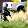 A SWAT member runs across the street to cover a house where a man has broken in drunk and is armed with a gun near Euclid Ave and Quinn in Boulder, Colorado October 2, 2012.  DAILY CAMERA/ MARK LEFFINGWELL