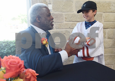 Earl Campbell speaks to his fan Brandt Crenshaw, 8, of Bullard after a Thursday press conference at Texas Spine & Joint Hospital announcing a new partnership called the Project Rose Research Institute. The program will be located on the second floor of the hospital and is anticipated to open in 2017.  (Sarah A. Miller/Tyler Morning Telegraph)