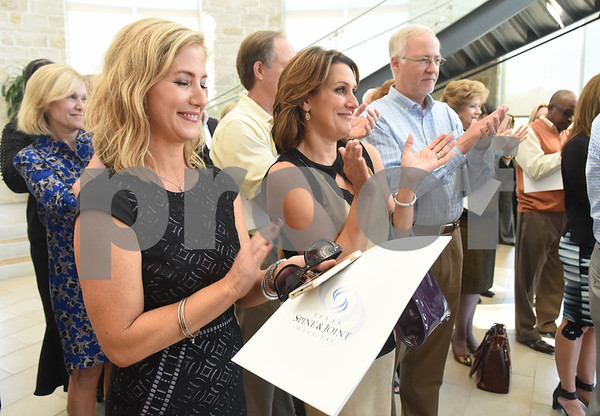 The crowd applauds after Tyler natives Gary Baxter and Earl Campbell speak during a Thursday press conference at Texas Spine & Joint Hospital announcing a new partnership called the Project Rose Research Institute. The program will be located on the second floor of the hospital and is anticipated to open in 2017.  (Sarah A. Miller/Tyler Morning Telegraph)