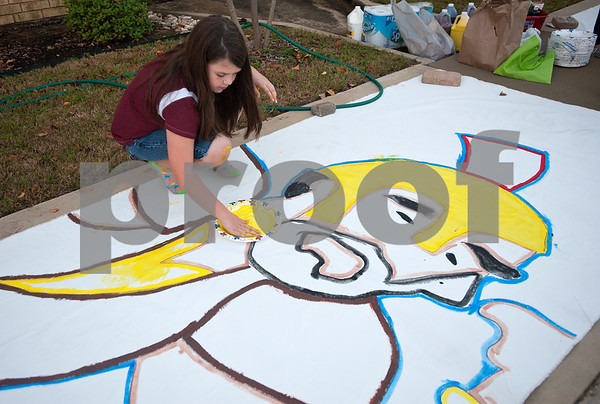 """photo by Sarah A. Miller/Tyler Morning Telegraph  Kayla Wells, 11, of Troup, helps paint a large picture during Fall Fest at Rose Heights Church in Tyler Wednesday evening that will be donated to the YMCA of Tyler on Thursday. The event included face painting, games, inflatables, hot dogs and hayrides and an appearance from Grayson Russell who was in the movie, """"Diary of a Wimpy Kid."""""""