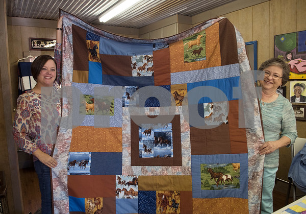 Lacey Strother and Linda Spates unfold a quilt with a horse-themed fabrics during a meet-up of the Sewing Sisters of Texas, a non-profit group of women whose main focus is making quilts for children of military members through the Seven Stars Foundation. The group meets at a gallery in Frankston to make quilts together. The majority of their fabrics and notions come from donations.   (Sarah A. Miller/Tyler Morning Telegraph)