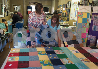 Lacey Strother and Kristy Clark show off the denim backing of a quilt during a meet-up of the Sewing Sisters of Texas, a non-profit group of women whose main focus is making quilts for children of military members through the Seven Stars Foundation. The group meets at a gallery in Frankston to make quilts together. The majority of their fabrics and notions come from donations.   (Sarah A. Miller/Tyler Morning Telegraph)