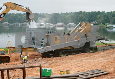 photo by Sarah A. Miller/Tyler Morning Telegraph  Workers use a DeWind One-Pass Trenching machine to mix soil, cement and clay together to create a new barrier along Lake Tyler in Whitehouse Wednesday.