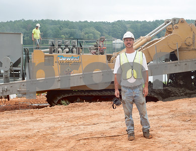 photo by Sarah A. Miller/Tyler Morning Telegraph  Greg DeWind is pictured at Lake Tyler Wednesday in front of the DeWind One-Pass Trenching machine he invented. The machine is currently being used at the Lake Tyler dam in Whitehouse to mix soil, cement and clay together to create a new barrier.