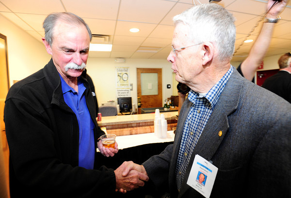 David Wineland (L) shakes hands with colleague Fred Wells (R) after a news conference in Boulder, Colorado after learning he and Serge Haroche of France were awarded the 2012 Nobel Prize in Physics, October 9, 2012.  The two men were awarded the prize for finding ways to measure quantum particles without destroying them, which could make it possible to build a new kind of computer far more powerful than any seen before.  DAILY CAMERA/ Mark Leffingwell