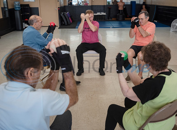 Parkinson's patients work with instructor Brandon Jones, center, during the Rock Steady Boxing Program for Parkinson's disease patients at Tyler Kung Fu ad Fitness on Monday, Oct. 7, 2019. Parkinson's patients in the class train in boxing drills and maneuvers such as hitting punching bags and shuffling along a straight line to help them build strength and balance.  (Sarah A. Miller/Tyler Morning Telegraph)