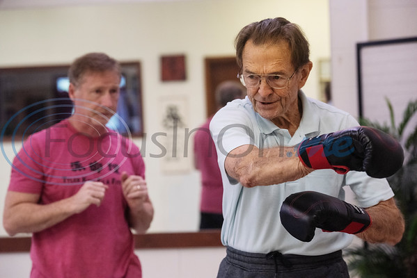 Tyler Kung Fu ad Fitness owner Brandon Jones, left, instructs Neal Pock, a retired doctor, through an obstacle course during the Rock Steady Boxing Program for Parkinson's disease patients at Tyler Kung Fu ad Fitness on Monday, Oct. 7, 2019. Parkinson's patients in the class train in boxing drills and maneuvers such as hitting punching bags and shuffling along a straight line to help them build strength and balance.  (Sarah A. Miller/Tyler Morning Telegraph)