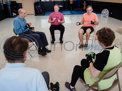 Parkinson's patients Neal Pock, Dick Kronenberg, instructor Brandon Jones, patients Connie Hudson and Joyce Stanley squeeze balls during the Rock Steady Boxing Program for Parkinson's disease patients at Tyler Kung Fu ad Fitness on Monday, Oct. 7, 2019. Parkinson's patients in the class train in boxing drills and maneuvers such as hitting punching bags and shuffling along a straight line to help them build strength and balance.  (Sarah A. Miller/Tyler Morning Telegraph)