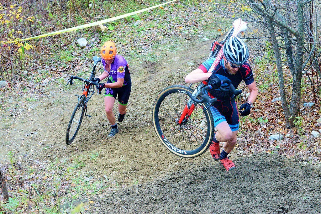 . Cyclists in the Masters race carry their bikes up a dirt hill at Willow Park during the 10th annual Wicked Creepy Cyclocross Race on Sunday. Oct. 30, 2016. Makayla McGeeney-Bennington Banner.