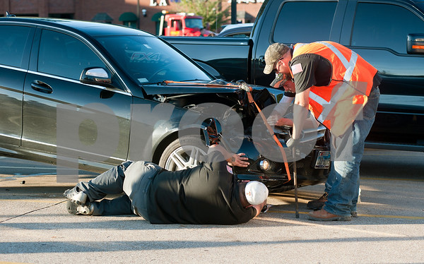 photo by Sarah A. Miller/Tyler Morning Telegraph  Men work on a car involved in a six vehicle accident  on Loop 323 in Tyler Friday afternoon.