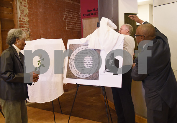 """Captoria Johnson, wife of Willie Neal Johnson, accepts a rose as Mayor Martin Heines and city councilman Darryl Bowdre unveil a Half Mile of History marker for Willie Neal Johnson in Downtown Tyler Tuesday Jan. 10, 2016. Johnson was a gospel singer from Tyler known as """"Country Boy."""" A stone for Arthur """"Dooley"""" Wilson, an actor, was also unveiled Tuesday. The Half Mile of History is a permanent, outdoor, half-mile loop that surrounds the Square in the heart of Downtown Tyler.  Stone plaques are placed in the sidewalk along the Half Mile of History to commemorate significant people, places or events.  (Sarah A. Miller/Tyler Morning Telegraph)"""