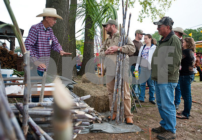 photo by Sarah A. Miller/Tyler Morning Telegraph  Doug Ford of Arrowhead Farm in Hallsville, left, teaches Tim Russell of Rusk and his brother James Russell of Houston how to plant and care for the ribbon cane stalks they purchased from him at the Henderson Heritage Syrup Festival Saturday in Henderson, Texas. The festival commemorates the tradition of ribbon cane syrup making with a live demonstration using antique mule powered equipment to produce old fashioned cane syrup. The one day festival features other folk artist demonstrations including soap making, rope making, basket making, blacksmithing, wood carving, quilting, and other old-time survival skills.