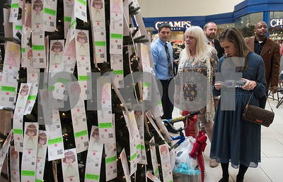 People look at children's wishes for presents on the Angel Tree during The Salvation Army Christmas Kick-Off Friday Nov. 10, 2017 at Broadway Square Mall. The Christmas Kick-Off launches The Salvation Army's 2017 Kettle and Angel Tree season. Volunteers will have the chance to ring bells with the iconic red kettle at over 37 locations around Smith County this year. The Salvation Army also registered over 2,500 children as Angels on the Angel Tree this year.   (Sarah A. Miller/Tyler Morning Telegraph)