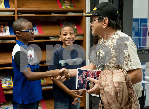 photo by Sarah A. Miller/Tyler Morning Telegraph  Bell Elementary School fourth graders Jordan Vaughn, 9, and Joseph Hickman, 9, greet William Norman, a Marine veteran from Granbury at a reception after their Veterans Day program at the school in Tyler. Vaughn has two grandchildren who attend the school.