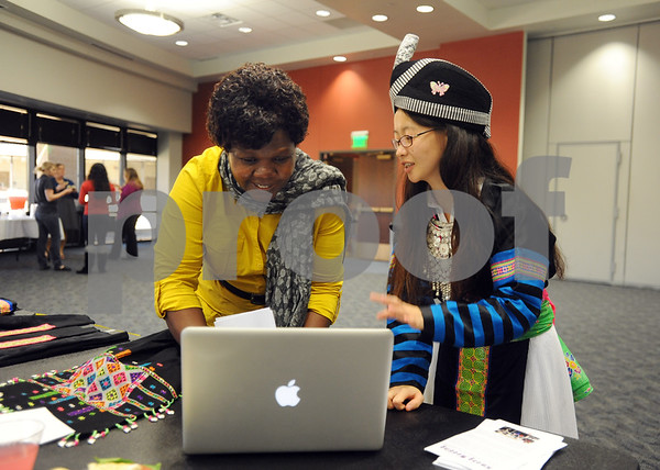 photo by Sarah A. Miller/Tyler Morning Telegraph  University of Texas at Tyler graduate student Kue Xiong of Wisconsin, right, teaches professor Dr. Fletcher Njororai, left, about Hmong culture at the Henna, Dress and Adornment Workshop held Wednesday at UT-Tyler. The event showcased articles of clothing from different cultures, jewelry and henna tattoos.
