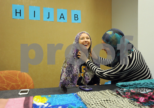 photo by Sarah A. Miller/Tyler Morning Telegraph  University of Texas at Tyler junior Brittany McKissack of Plano, left, has help putting on a hijab from sophomore Uroosa Khalid of Tyler at the Henna, Dress and Adornment Workshop held Wednesday at UT-Tyler. A hijab is a piece of fabric that covers a woman's hair and neck. It is commonly worn by women of Muslim faith as a an article of modesty.