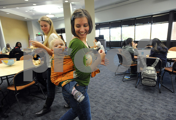 photo by Sarah A. Miller/Tyler Morning Telegraph  Brittany Smith of the University of Texas at Tyler student group Reform University Fellowship tries out am African baby wrap for her son Jonah, age 1, at the Henna, Dress and Adornment Workshop held Wednesday at UT-Tyler.