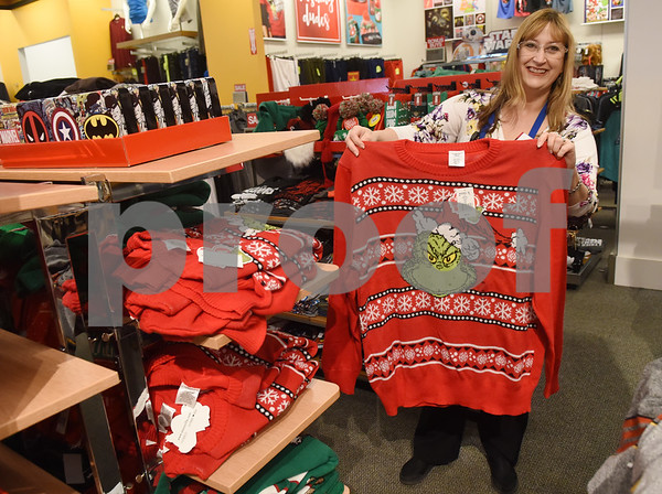 Kohl's store manager Janie Mayo holds up a men's Christmas sweater at her store in Tyler Tuesday Nov. 16, 2016. Kohl's now has extended holiday shopping hours and a smartphone app for customers.  (Sarah A. Miller/Tyler Morning Telegraph)