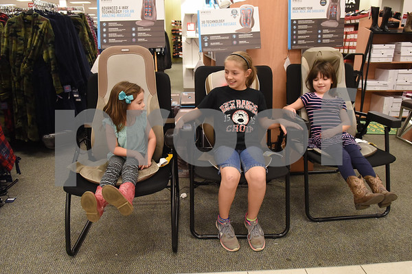 Claire Hitt, 4, Haylee Hitt, 11, and Olivia Hitt, 6, of Tyler, try out Homemedics massage pads at Kohl's in Tyler Tuesday Nov. 16, 2016. Kohl's now has extended holiday shopping hours and a smartphone app for customers.  (Sarah A. Miller/Tyler Morning Telegraph)