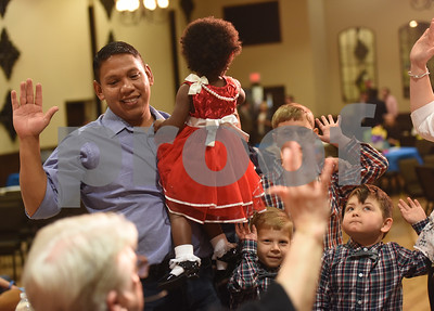 Rafael Gonzalez of Jacksonville raises his right hand as he holds his newly adopted daughter Mia Joy, 2, during an adoption event held by the Texas Department of Family and Protective Services at Rose Heights Church in Tyler Friday Nov. 18, 2016. November is National Adoption Awareness Month.  (Sarah A. Miller/Tyler Morning Telegraph)