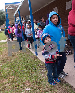 Ramiro Martinez, 4, and Eberardo Martinez, 9, wait in line to try on new winter coats at the North Tyler Day Nursery gymnasium, 3000 N. Border Ave. Saturday Nov. 21, 2015. PATH handed out new and gently-used coats to Smith County children and teens in need as part of their Coast for Kids program. Over 1,000 children were preregistered to receive coats Saturday.  (Sarah A. Miller/Tyler Morning Telegraph)
