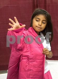 Valeria Rodriguez, 7, tries on a pink coat at PATH Coats for Kids at the North Tyler Day Nursery gymnasium, 3000 N. Border Ave. Saturday Nov. 21, 2015. PATH handed out new and gently-used coats to Smith County children and teens in need. Over 1,000 children were preregistered to receive coats Saturday.  (Sarah A. Miller/Tyler Morning Telegraph)