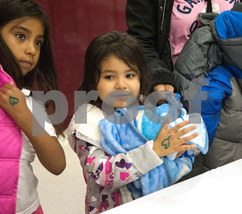Valeria Rodriguez, 7, tries on a pink coat and her sister Jennifer Rodriguez, 6, holds a new blanket at PATH Coats for Kids at the North Tyler Day Nursery gymnasium, 3000 N. Border Ave. Saturday Nov. 21, 2015. PATH handed out new and gently-used coats to Smith County children and teens in need. Over 1,000 children were preregistered to receive coats Saturday.  (Sarah A. Miller/Tyler Morning Telegraph)