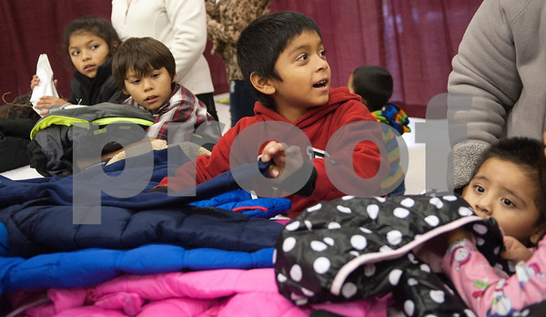 Emanuel Sanchez, 7, center, picks out a coat he likes at PATH Coats for Kids at the North Tyler Day Nursery gymnasium, 3000 N. Border Ave. Saturday Nov. 21, 2015. PATH handed out new and gently-used coats to Smith County children and teens in need. Over 1,000 children were preregistered to receive coats Saturday.  (Sarah A. Miller/Tyler Morning Telegraph)