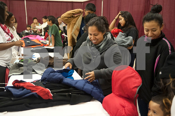 Maria Segura, center, smiles as she sorts through coats for her children to try on at the North Tyler Day Nursery gymnasium, 3000 N. Border Ave. Saturday Nov. 21, 2015. PATH handed out new and gently-used coats to Smith County children and teens in need as part of their Coast for Kids program.   (Sarah A. Miller/Tyler Morning Telegraph)