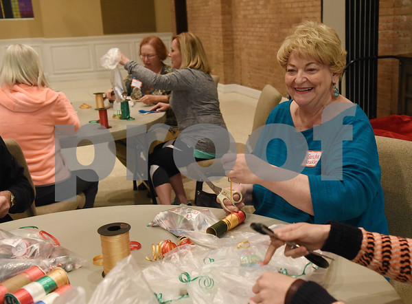 Sandra Weakley curls ribbons for bags inside stockings Tuesday night at Marvin United Methodist Church. The 525 hand made stockings will be given to children at Saint Paul's Foundation in Tyler for Christmas.  (Sarah A. Miller/Tyler Morning Telegraph)