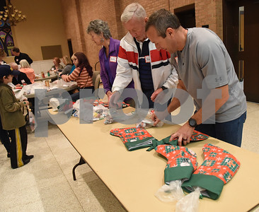 Volunteers including Terry Hawkins, right place goodie bags into stockings Tuesday night at Marvin United Methodist Church.  (Sarah A. Miller/Tyler Morning Telegraph)