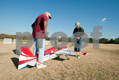 photo by Sarah A. Miller/Tyler Morning Telegraph  Jim Day of Whitehouse, left, and Bit McCray, right, prepare to fly a remote controlled model airplane at Northside RC Airpark in Tyler Tuesday afternoon. City of Tyler staff members are making videos of Tyler's many parks and their amenities. The videos are accessible via QR codes, which are posted on signs at the parks.