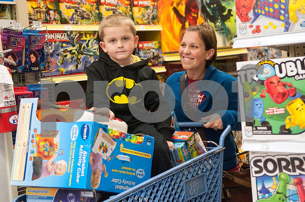 Benjamin Nowell, 4, of Flint, rides in a shopping cart filled with toys pushed by his mother Josey Nowell at Toys R Us during Black Friday sales on Thanksgiving Day Thursday Nov. 26, 2015 in Tyler, Texas. Toys R Us opened at 5 p.m.   (Sarah A. Miller/Tyler Morning Telegraph)
