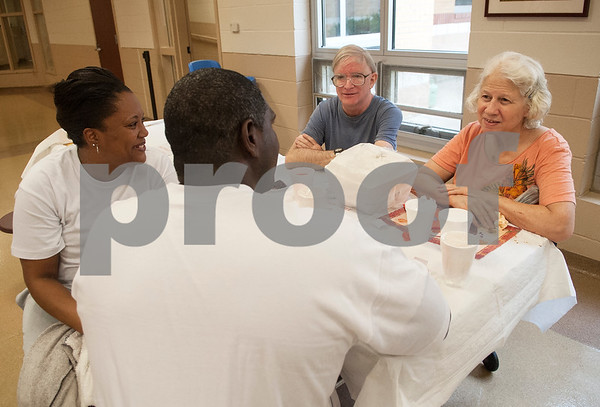 Volunteers Demetra Calico and Kerry Calico of Chapel Hill spend time with Paul Shaw and Janice Strain of Tyler as they eat Thanksgiving meals at the Salvation Army in Tyler Thursday Nov. 26, 2015.  (Sarah A. Miller/Tyler Morning Telegraph)