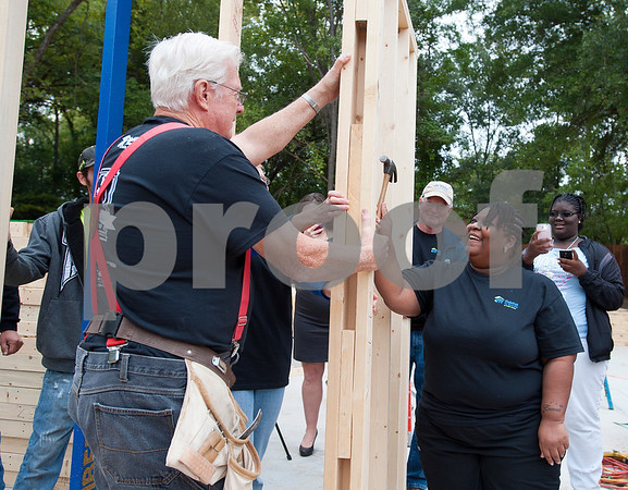 photo by Sarah A. Miller/Tyler Morning Telegraph  Habitat for Humanity volunteer Dennis Lorenz of Tyler, left, helps hold a section of house frame so new homeowner Cheresa Monmouth can nail the first nail in her future home on N. Spring Ave. in Tyler Monday. Monmouth's home is Habitat for Humanity's 100th home to be built in Smith County. Monmouth, a mother of two, will purchase the 100th home with a 30-year no-interest mortgage held by Smith County Habitat. The home will be built in 100 working hours, beginning with the raising of the walls.