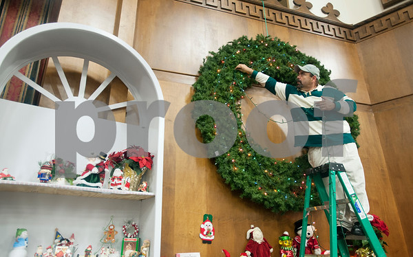 photo by Sarah A. Miller/Tyler Morning Telegraph  Alberto Sustaita hangs lights on a large wreath in Christmas decoration display at the The Store at Cornerstone in Tyler Wednesday Nov. 5, 2014. East Texas Cornerstone Assistance Network  provides services to their clients such as rent assistance, vouchers for clothing, assistance finding jobs and counseling.