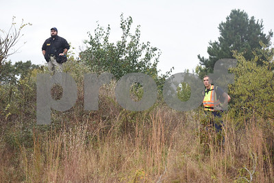 Smith County Sheriffs Office detective Justin Hall and Boone Savoca from the Alert Academy stand on high ground to watch volunteers canvass difficult terrain in Bullard on a public search for missing child Kayla Gomez-Orozco held Saturday morning. Hundreds of people gathered at Bullard High School at 7 a.m. to join in the effort to find the missing 10-year-old.  (Sarah A. Miller/Tyler Morning Telegraph)