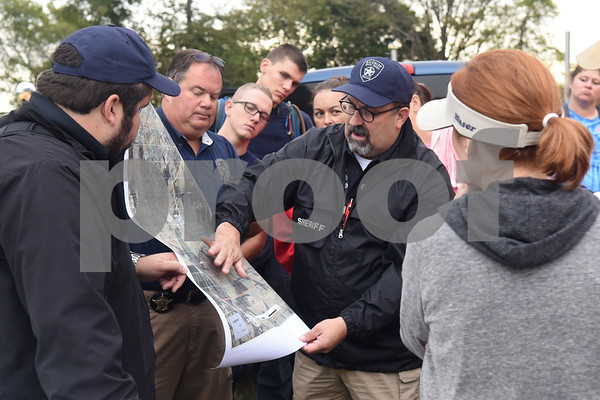 Smith County Sheriffs Office detective Justin Hall, sergeant Jim Fortner and detective Ron Rathbun use a map to show volunteers wooded areas and fields where they will search for missing child Kayla Gomez-Orozco Saturday morning in Bullard. Hundreds of people gathered at Bullard High School at 7 a.m. to join in the effort to find the missing 10-year-old.  (Sarah A. Miller/Tyler Morning Telegraph)