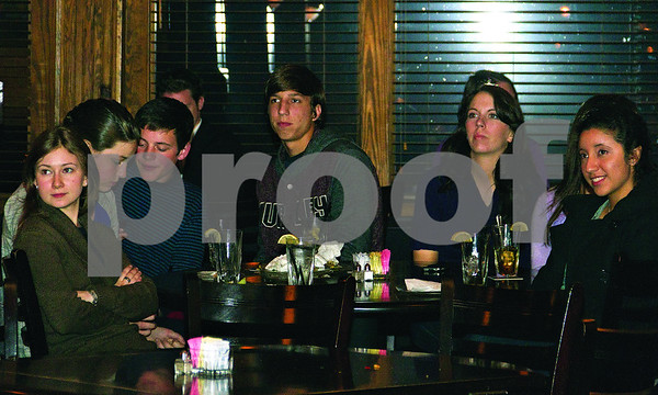 Young adults who volunteered in the Romney campaign gather at Rick's on the Square to watch election coverage.