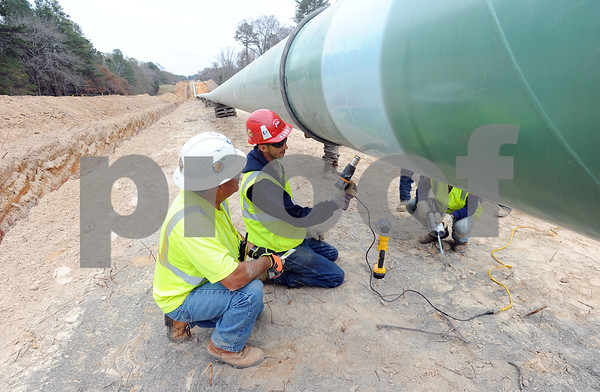 photo by Sarah A. Miller/Tyler Morning Telegraph  A worker makes a spot repair to the coating on a section of pipe before it is lowered into the ground Wednesday afternoon along the TransCanada Keystone XL Pipeline section two near Winona, Texas.