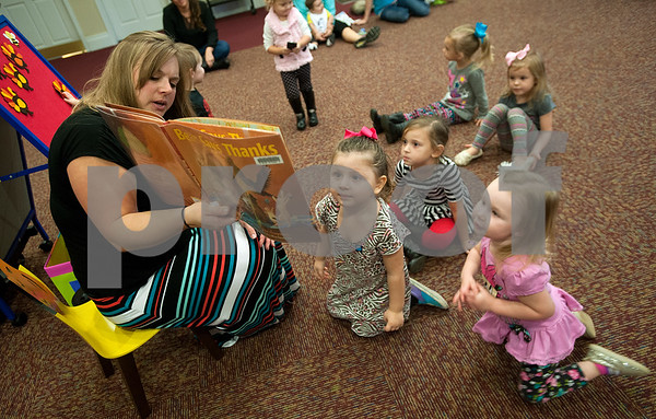Librarian Jenn Freeman reads a book to children during Baby & Me Fun Time at the McMillian Memorial Library in Overton Wednesday. The library is part of the Rusk County Library System.  (Sarah A. Miller/Tyler Morning Telegraph)