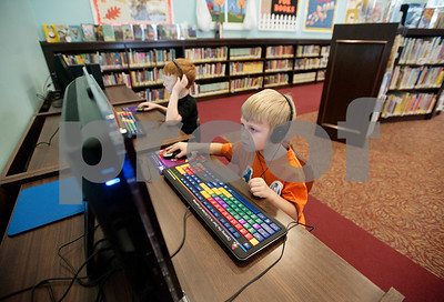 Brothers Conner Davis, 8, and Carston Davis, 5, of Overton, use computers in the children's area at the McMillian Memorial Library in Overton Wednesday. The library is part of the Rusk County Library System.  (Sarah A. Miller/Tyler Morning Telegraph)