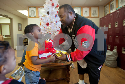 photo by Sarah A. Miller/Tyler Morning Telegraph  Jarvis Snipes hands his son Josiyah Snipes, 3, an Elmo toy to play with at Gateway to Hope Tuesday Dec. 16, 2014 in Tyler, Texas. Gateway to Hope is a resource day center for homeless people and those in need living in the Tyler and Smith County. Through a network of partners, Gateway to Hope provides resources such as clean showers, computer access, laundry facilities, transportation, food and clothing to the homeless and those in need.